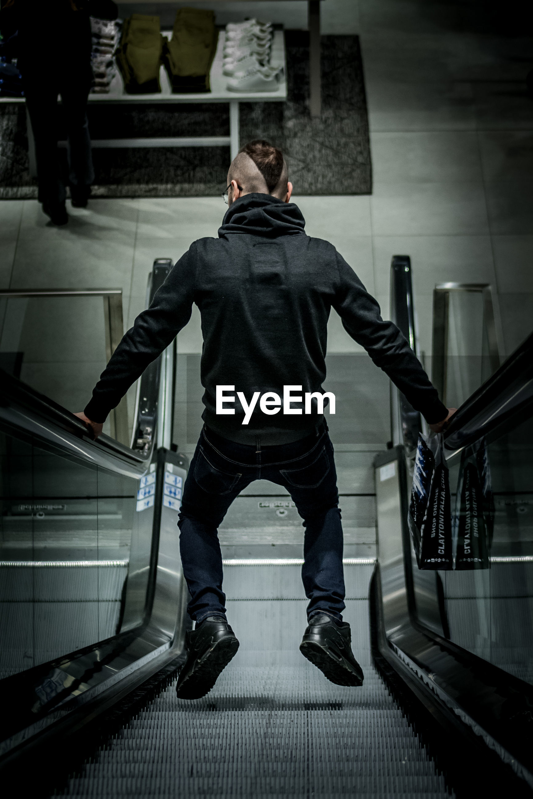Rear view of man holding escalator railings