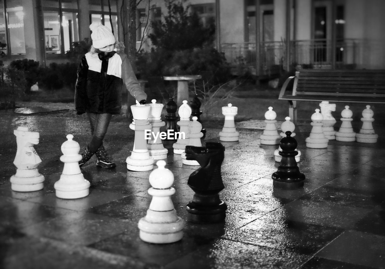 Full length of girl standing by chess board decoration at park during night