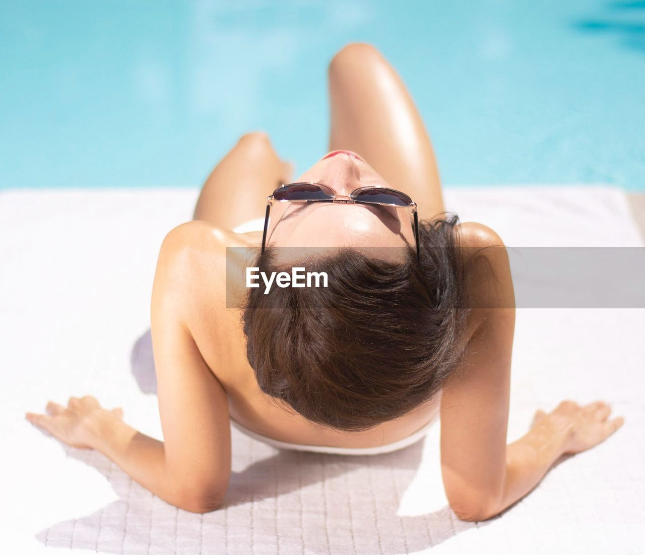MIDSECTION OF WOMAN LYING ON SWIMMING POOL