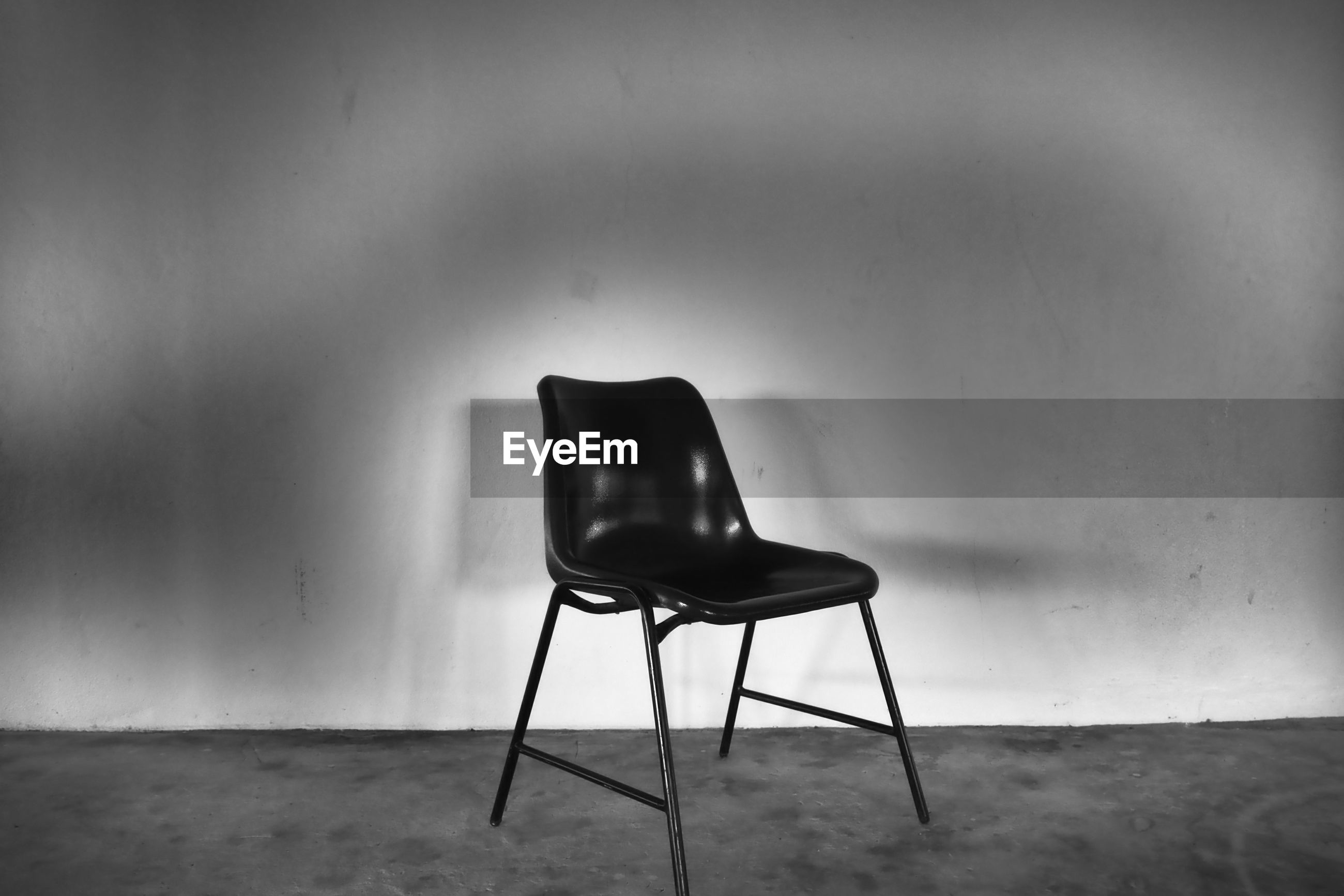 EMPTY CHAIR AND TABLE AGAINST WALL