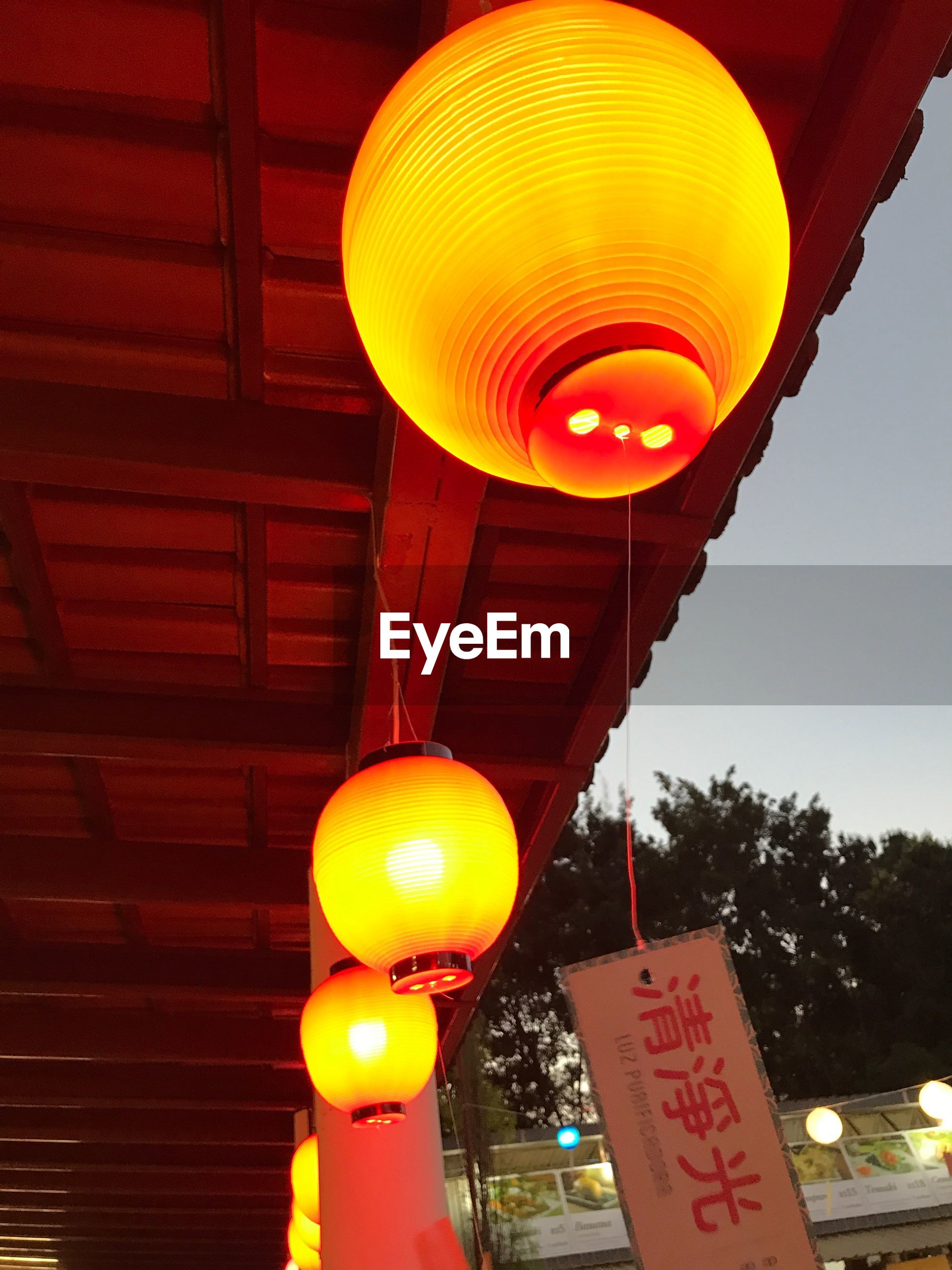 lighting equipment, lantern, illuminated, low angle view, orange color, hanging, chinese lantern, communication, no people, text, glowing, built structure, architecture, decoration, script, nature, outdoors, non-western script, sky, electricity, light, paper lantern, electric lamp, ceiling