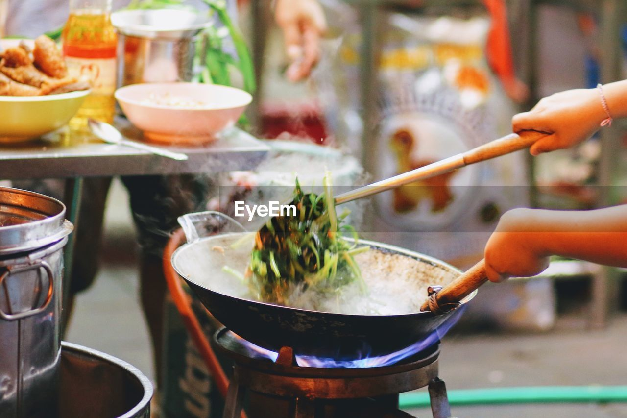Cropped Hand Of Woman Cooking Food On Stove At Street