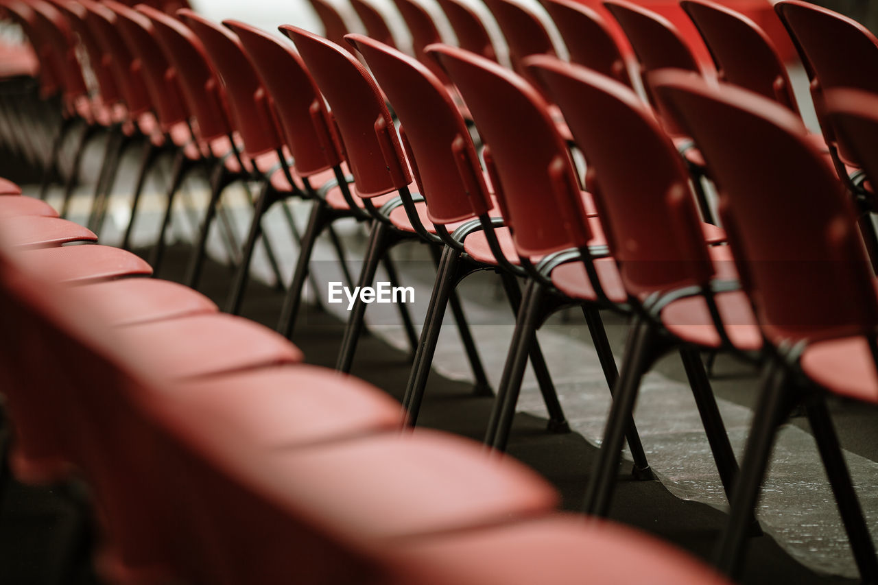 seat, in a row, selective focus, empty, chair, absence, repetition, arrangement, no people, day, large group of objects, order, side by side, red, close-up, indoors, abundance, relaxation, sunlight, high angle view, foldable