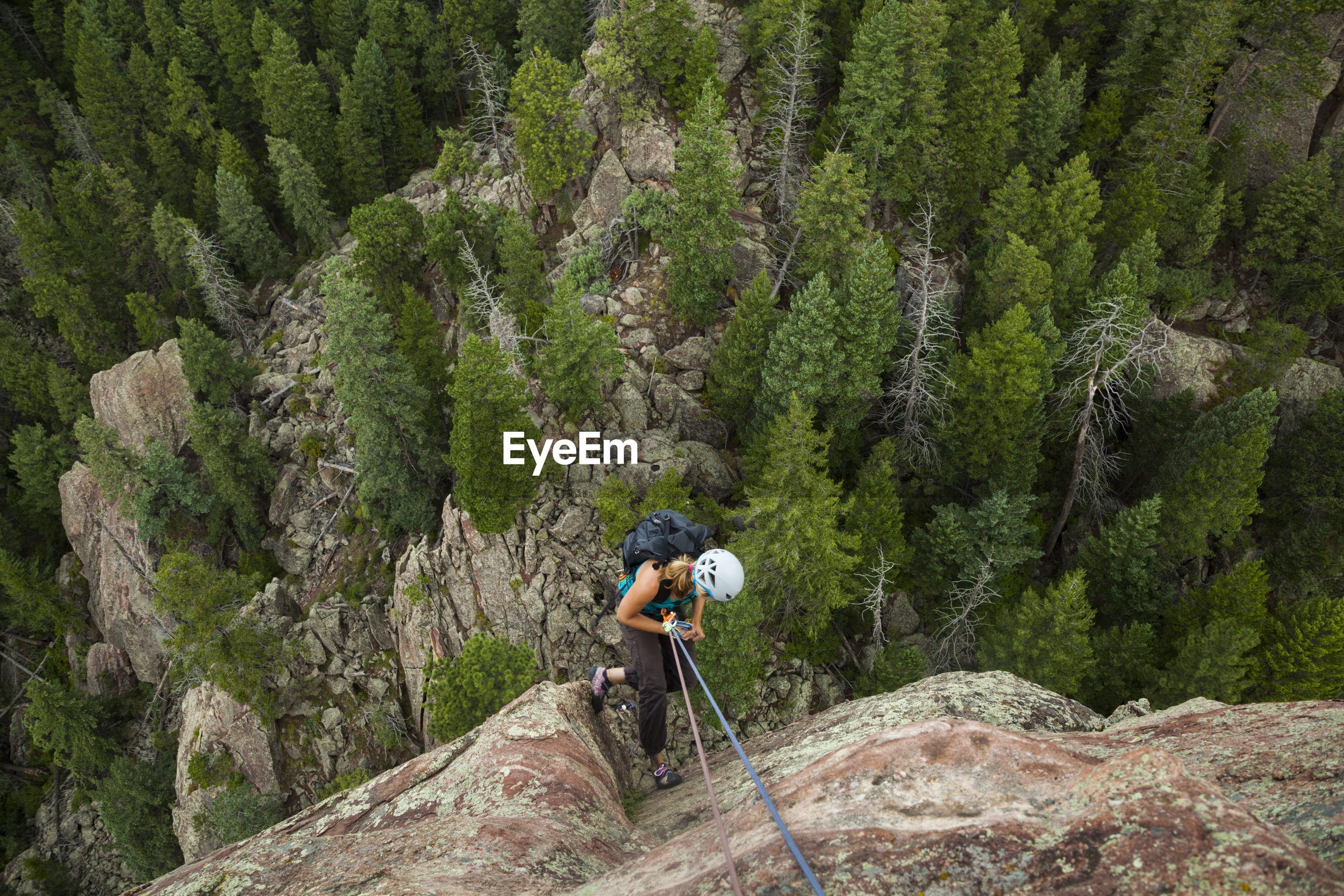 FULL LENGTH OF MAN ON ROCKS IN FOREST