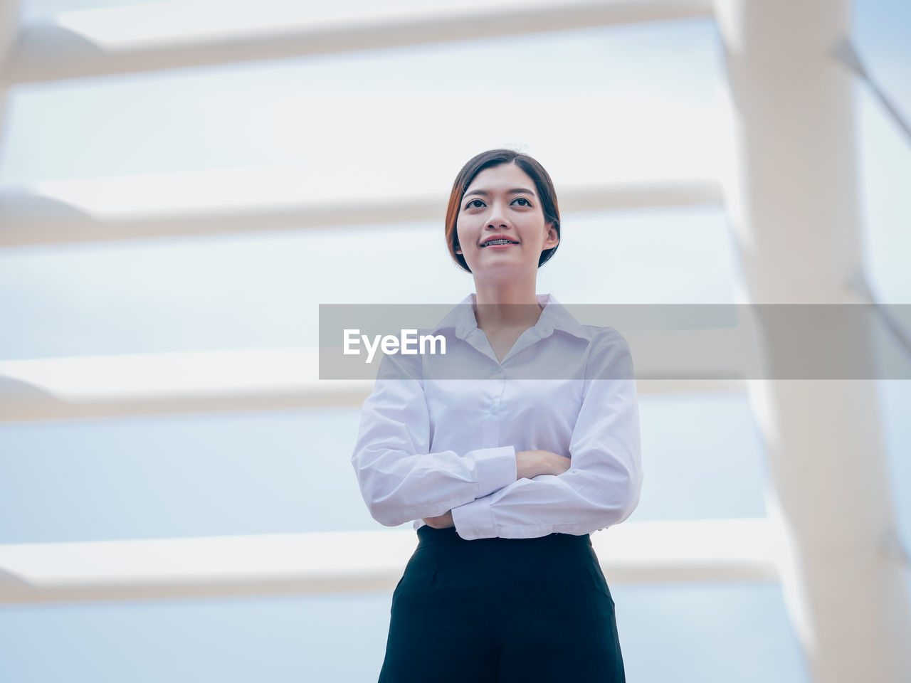 Smiling Young Woman With Arms Crossed Standing Against Building