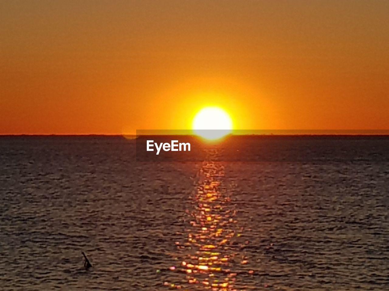 sun, sunset, orange color, sea, nature, scenics, sunlight, no people, sky, heat - temperature, tranquility, beauty in nature, clear sky, water, outdoors, landscape, horizon, beach, sand