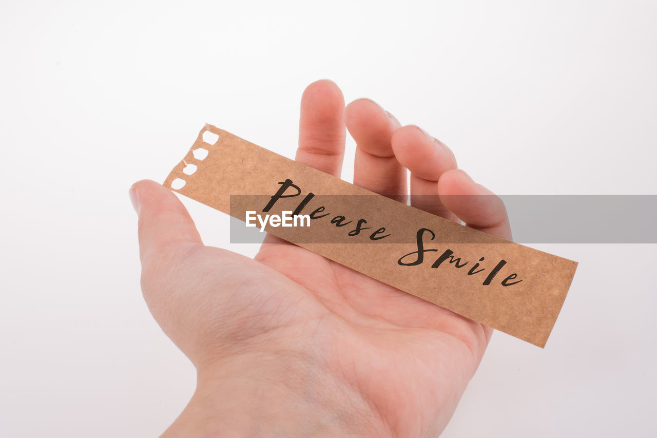 Cropped hand of person holding paper with text against white background