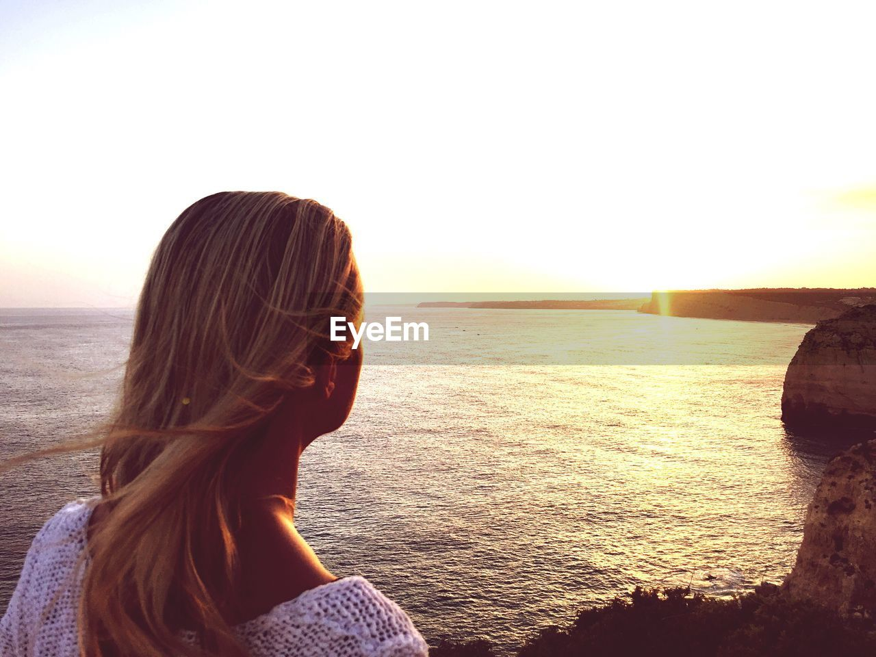 sea, sunset, one person, rear view, real people, water, leisure activity, nature, standing, horizon over water, scenics, long hair, sunlight, lifestyles, tranquil scene, sun, beach, women, tranquility, clear sky, beauty in nature, outdoors, wave, young adult, young women, sky, day, adult, people