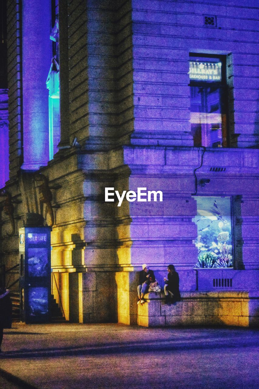 architecture, built structure, building exterior, real people, illuminated, night, group of people, lifestyles, women, walking, men, people, city, leisure activity, adult, building, incidental people, architectural column