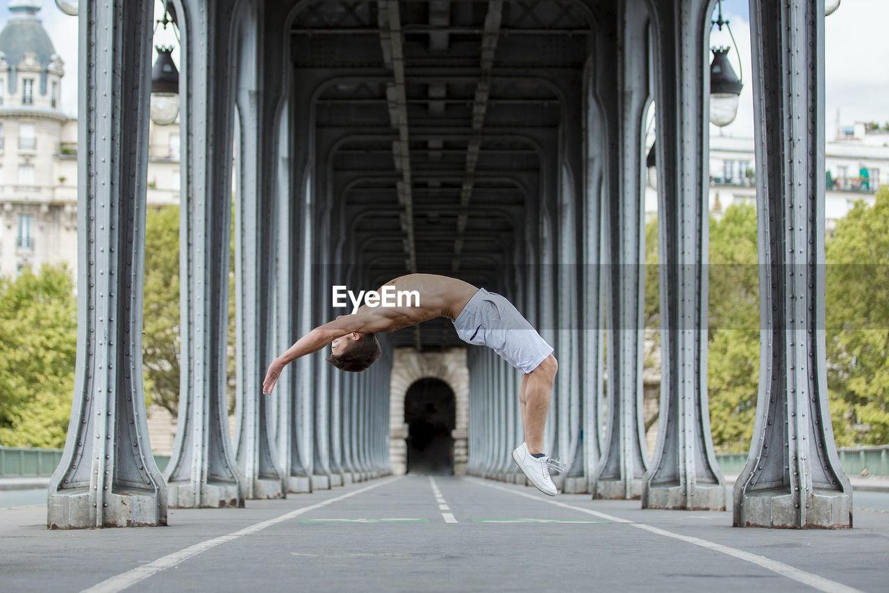 Side view full length of shirtless man jumping below bridge
