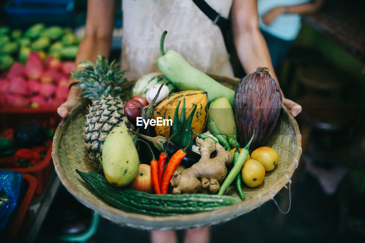 food, food and drink, freshness, one person, healthy eating, midsection, vegetable, real people, wellbeing, fruit, human hand, focus on foreground, day, holding, container, choice, hand, standing, selective focus, outdoors