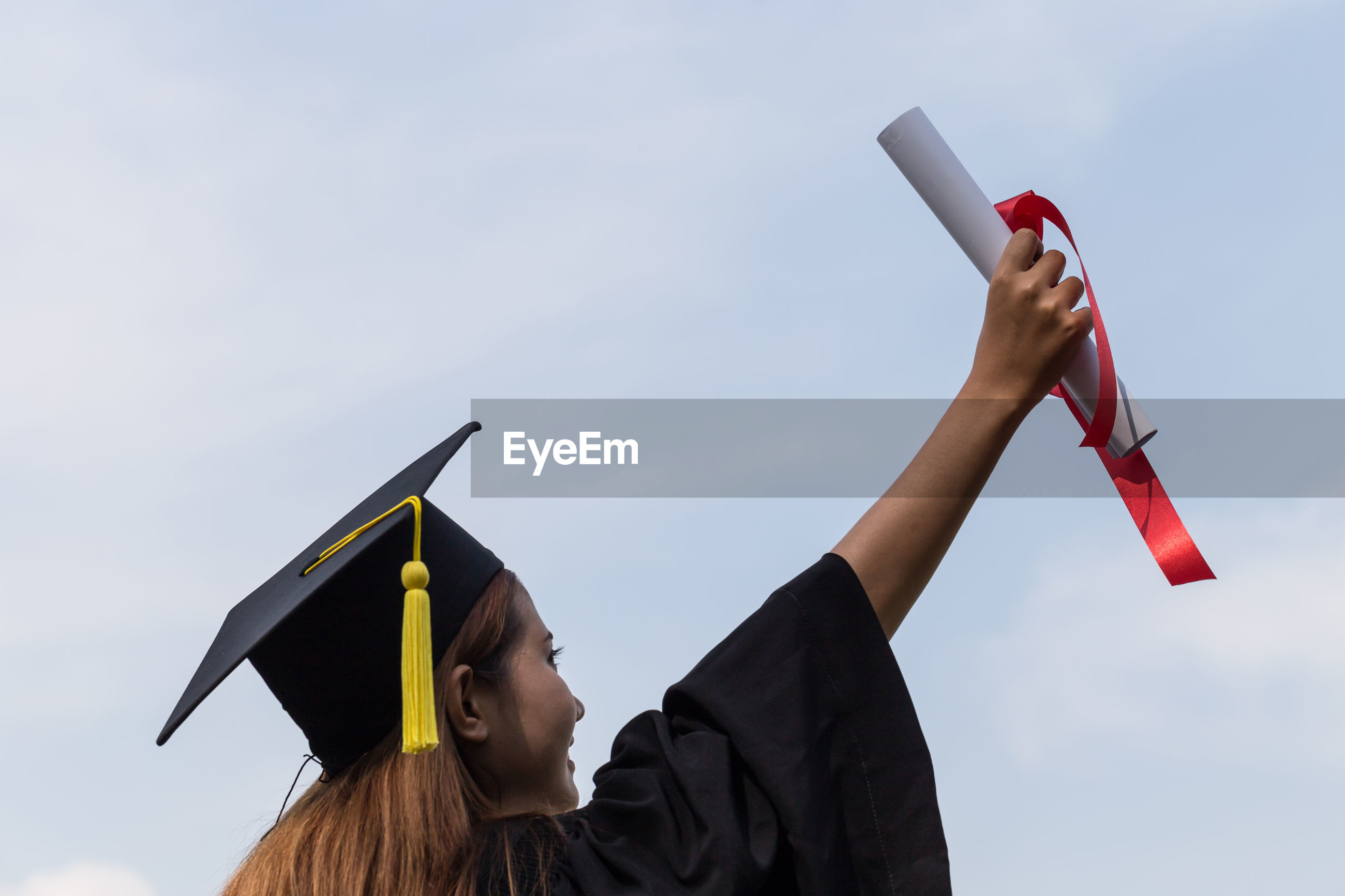 Rear view of woman holding diploma against sky