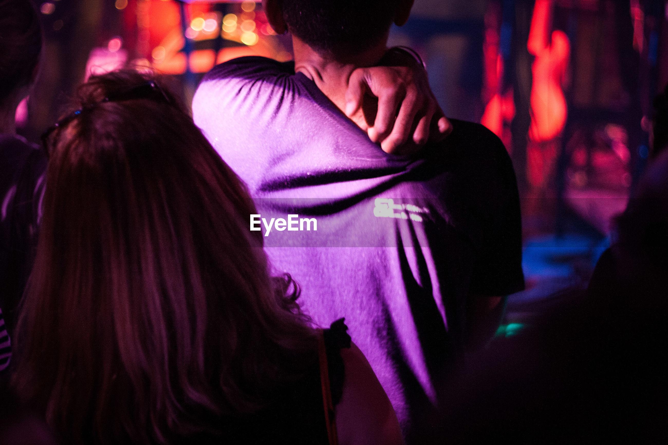REAR VIEW OF WOMAN DANCING AT NIGHT