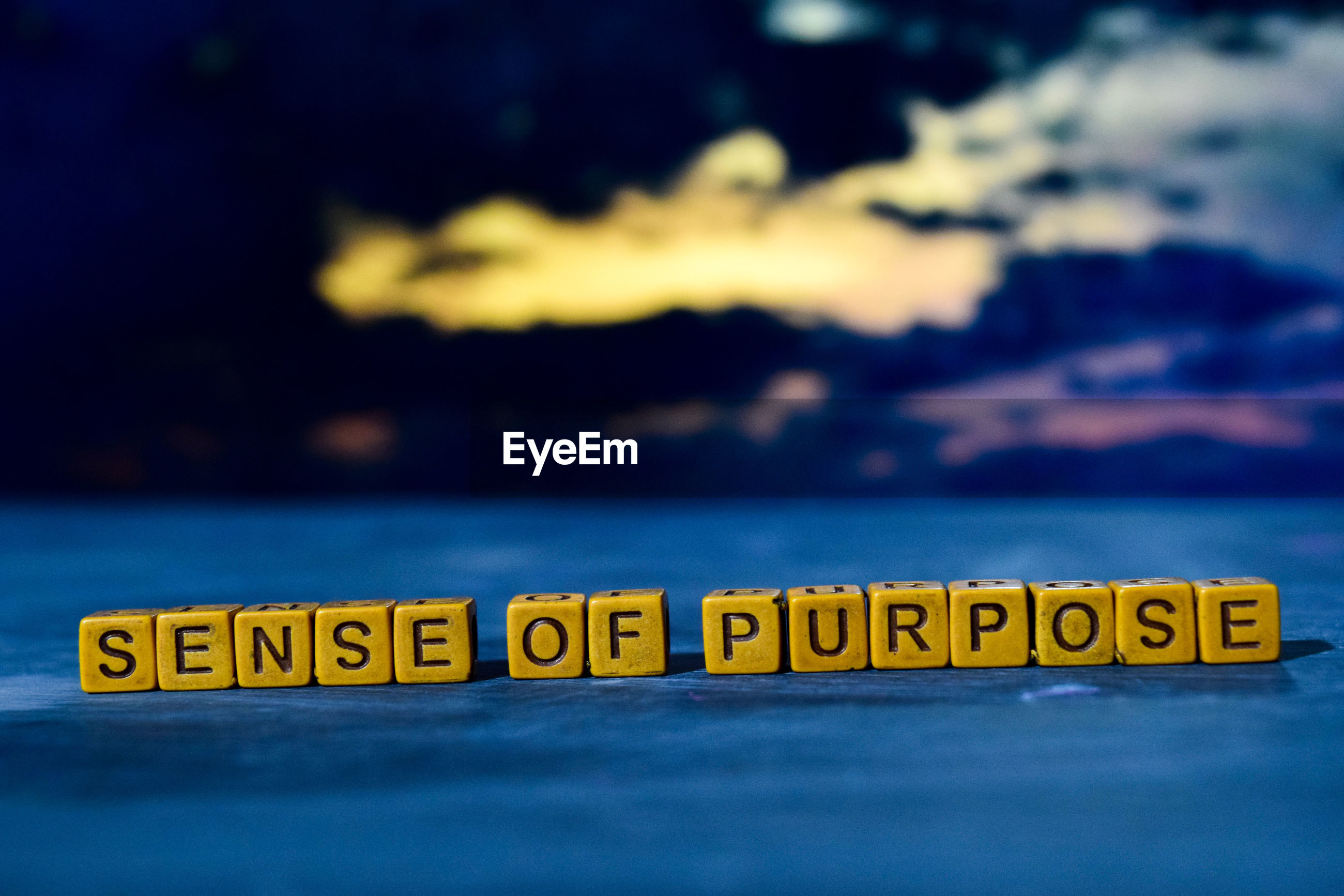 Sense of purpose text on blocks on surface against cloudy sky at dusk