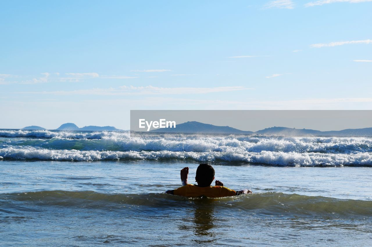 real people, sea, water, leisure activity, sky, nature, beauty in nature, men, lifestyles, waterfront, outdoors, rear view, scenics, wave, day, beach, horizon over water, people