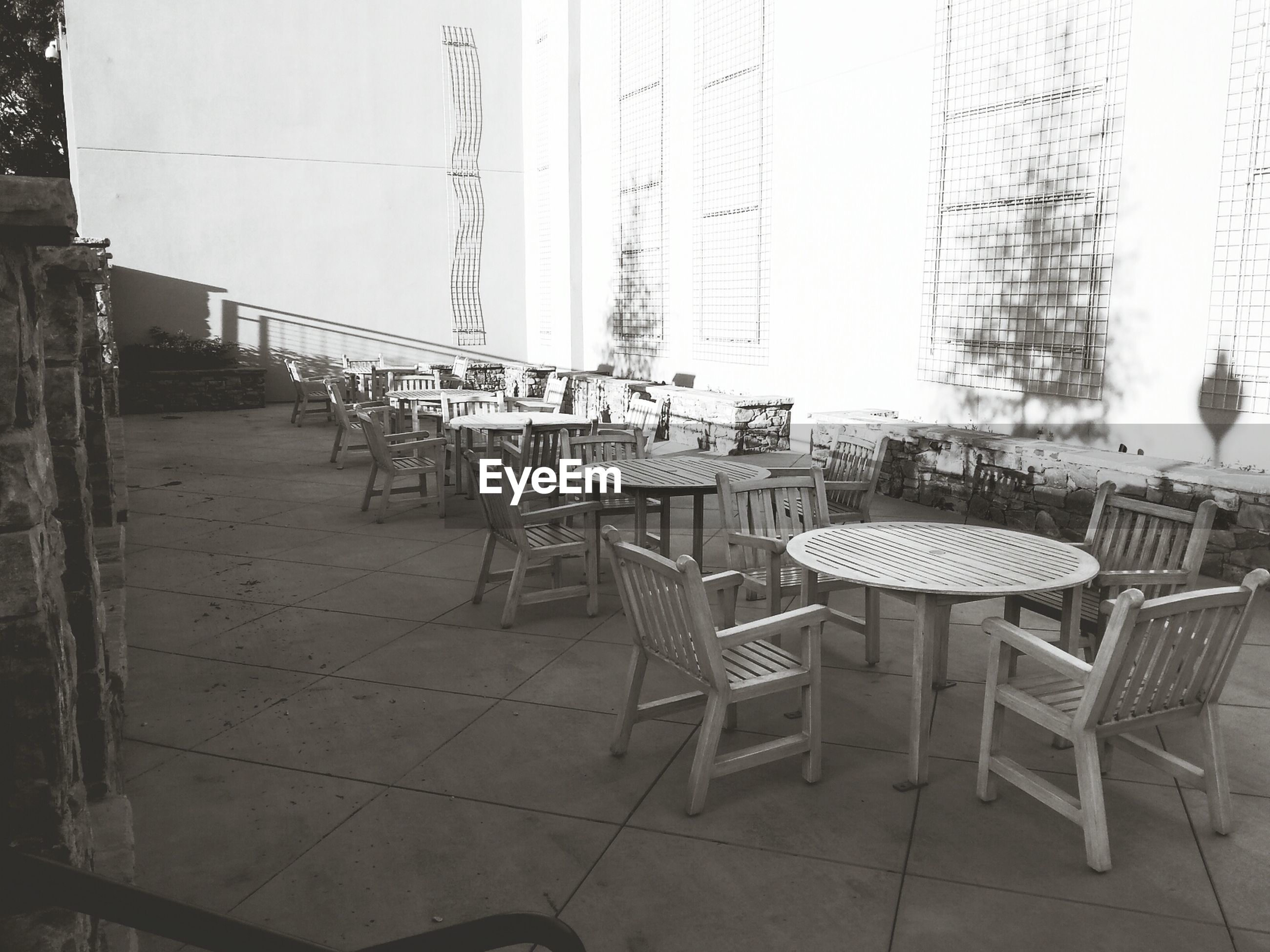 chair, empty, absence, built structure, architecture, table, seat, building exterior, sunlight, day, arrangement, bench, in a row, no people, wood - material, shadow, outdoors, furniture, wall - building feature, restaurant