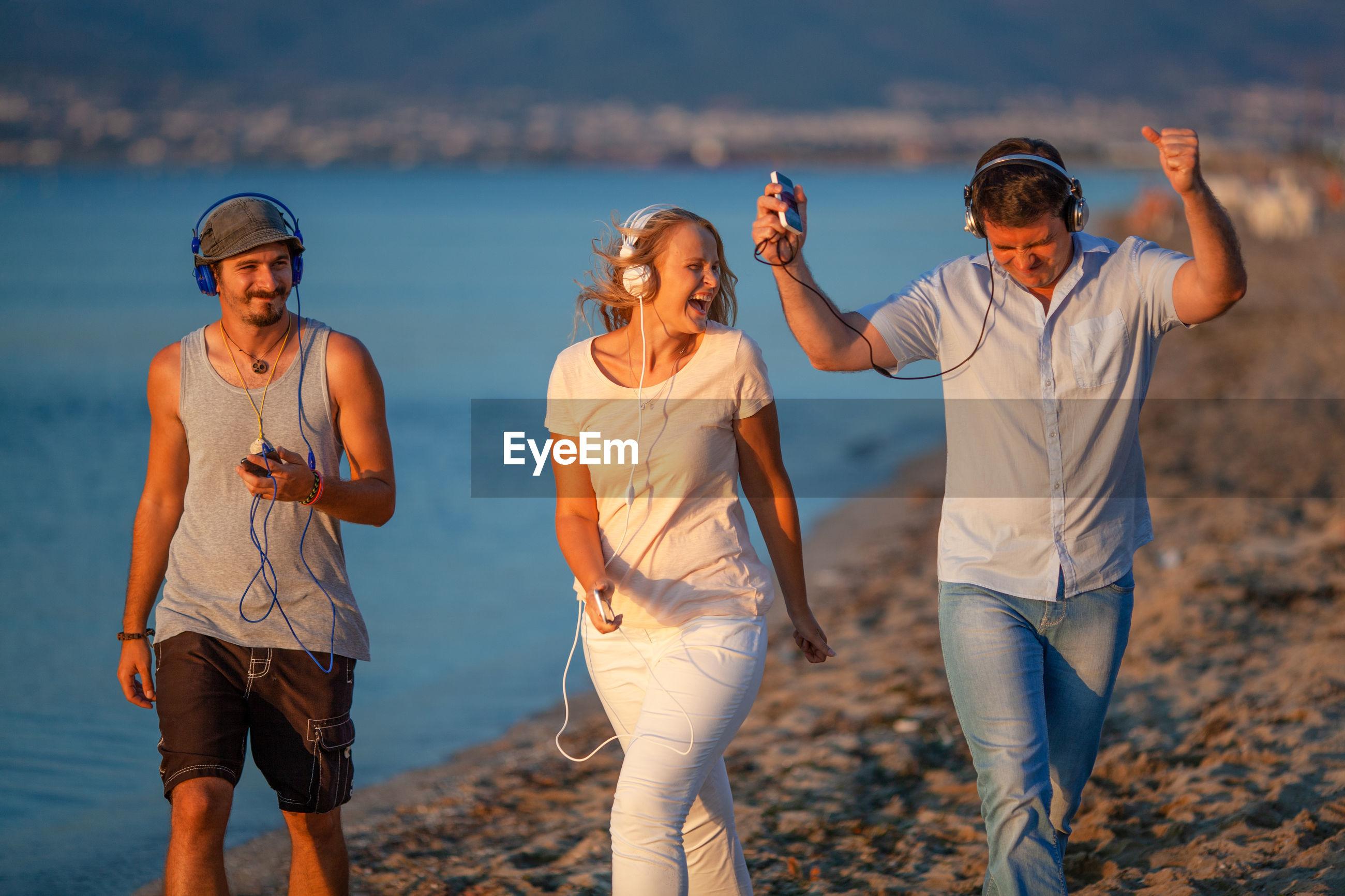 Cheerful friends walking at beach