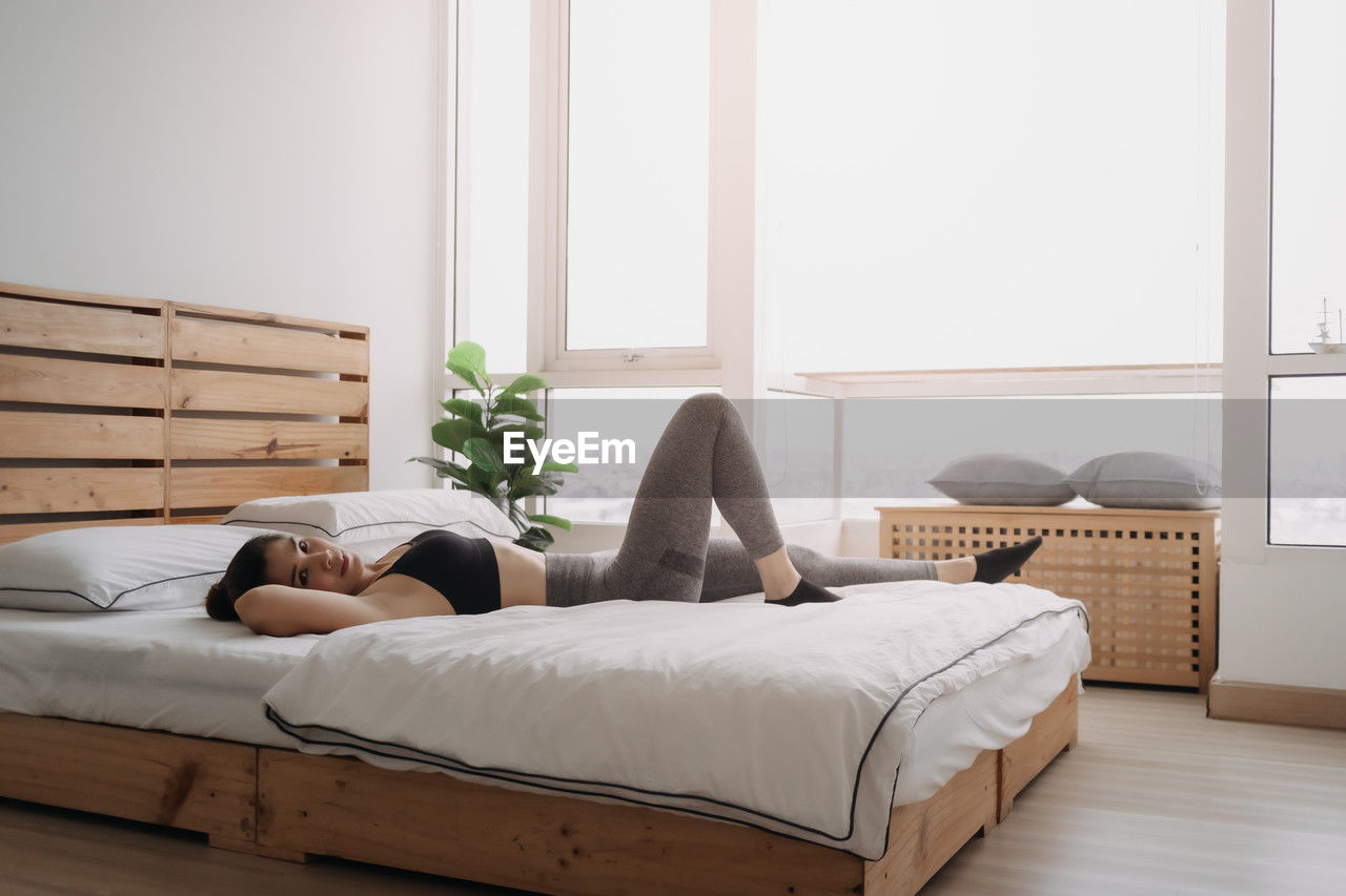 MAN SLEEPING ON BED BY WINDOW