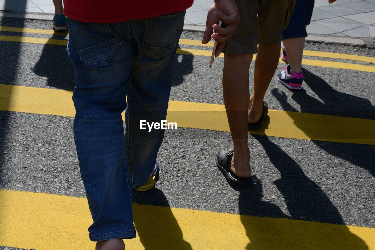 low section, real people, street, walking, human leg, road, men, standing, outdoors, yellow, day, two people, sunlight, shadow, lifestyles, togetherness, women, human body part, adult, people