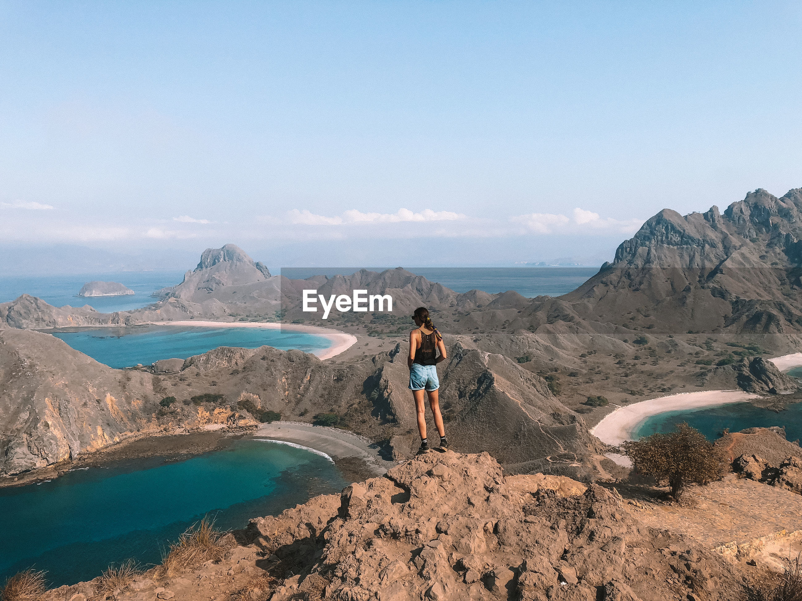 Full length of woman standing on mountain against blue sky