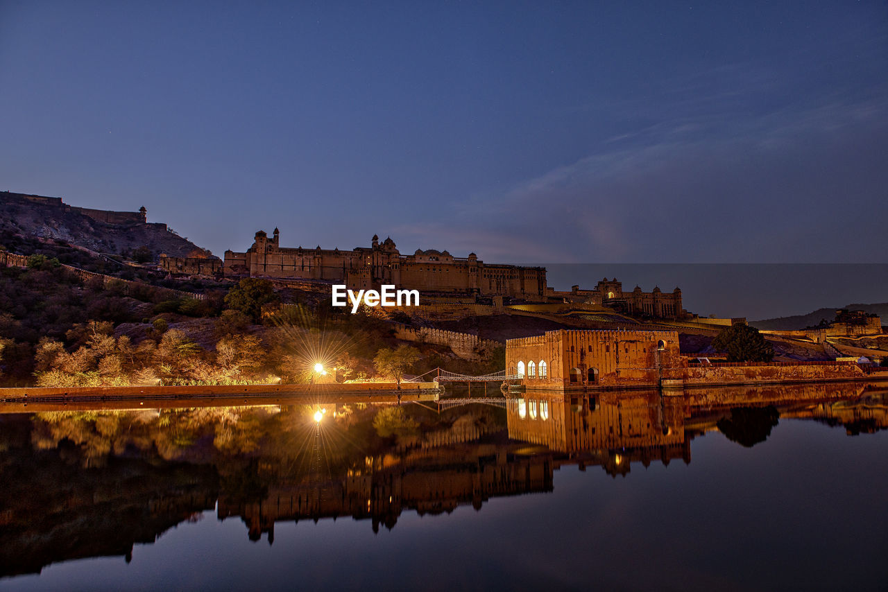 Reflection of historic buildings in lake at night
