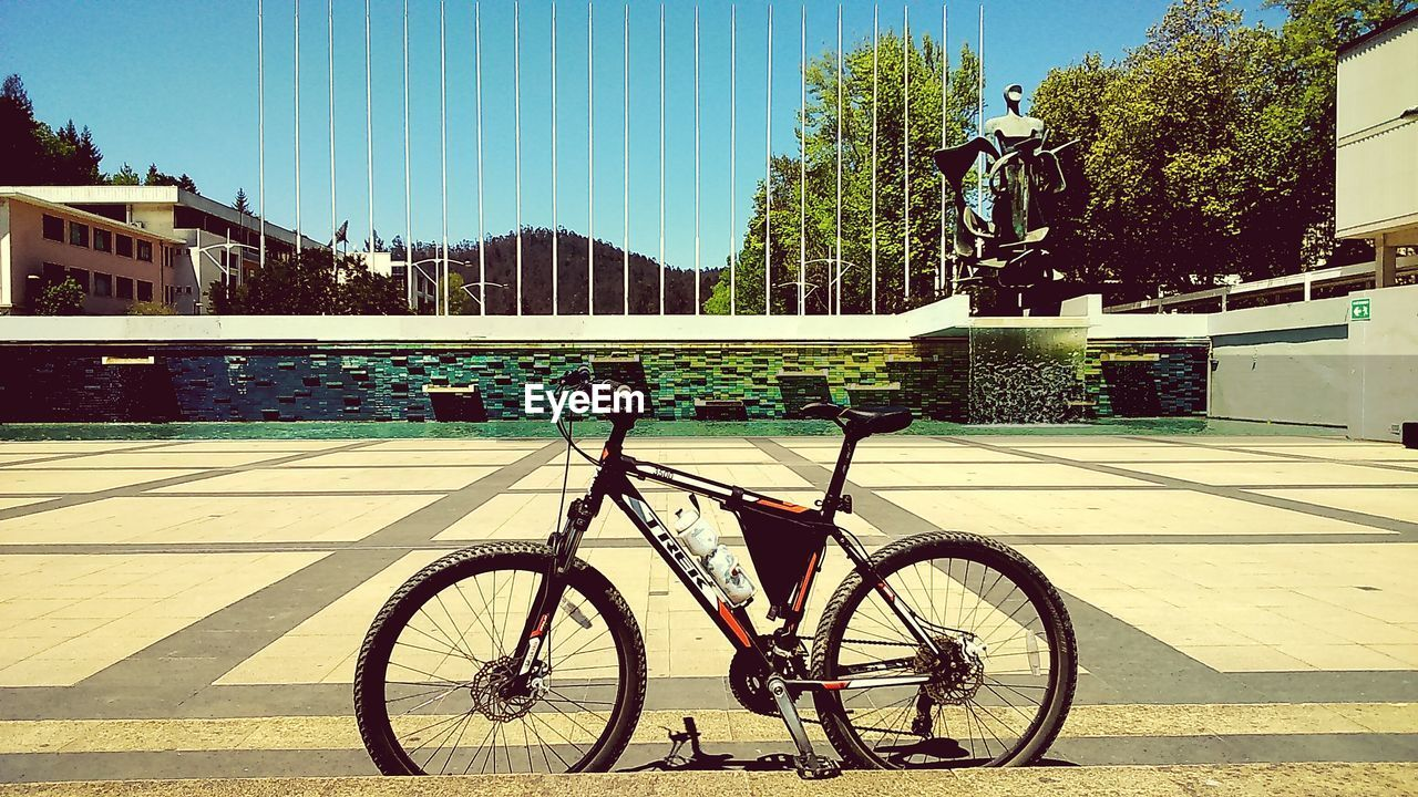 bicycle, mode of transport, transportation, land vehicle, stationary, day, outdoors, bicycle rack, sunlight, no people, tree, built structure, building exterior, shadow, architecture, water, sky