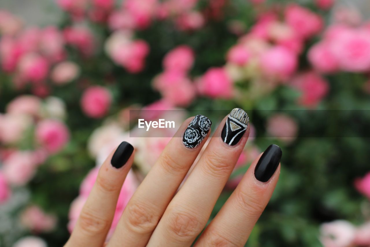 Cropped Hand Of Woman With Nail Polish Against Pink Flowers