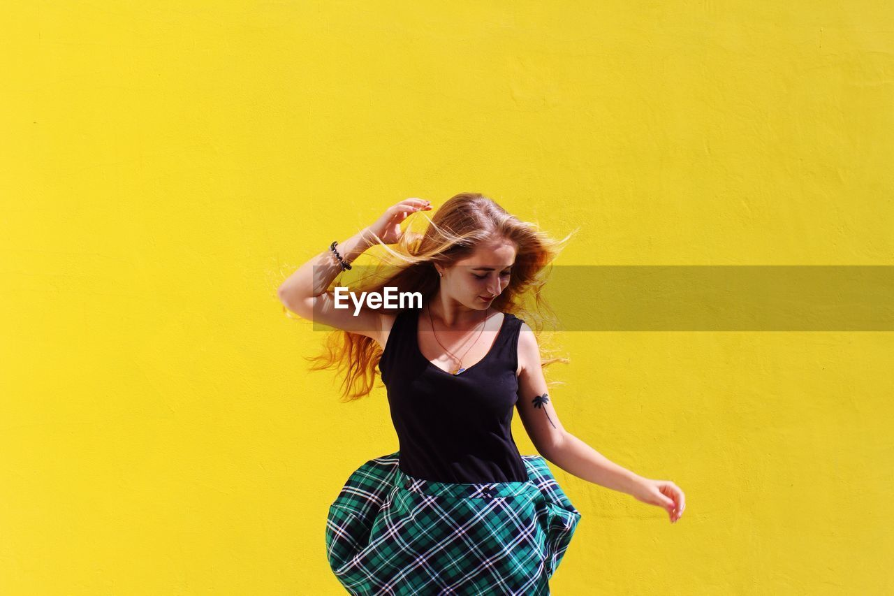 Beautiful Woman Looking Down While Standing By Yellow Wall