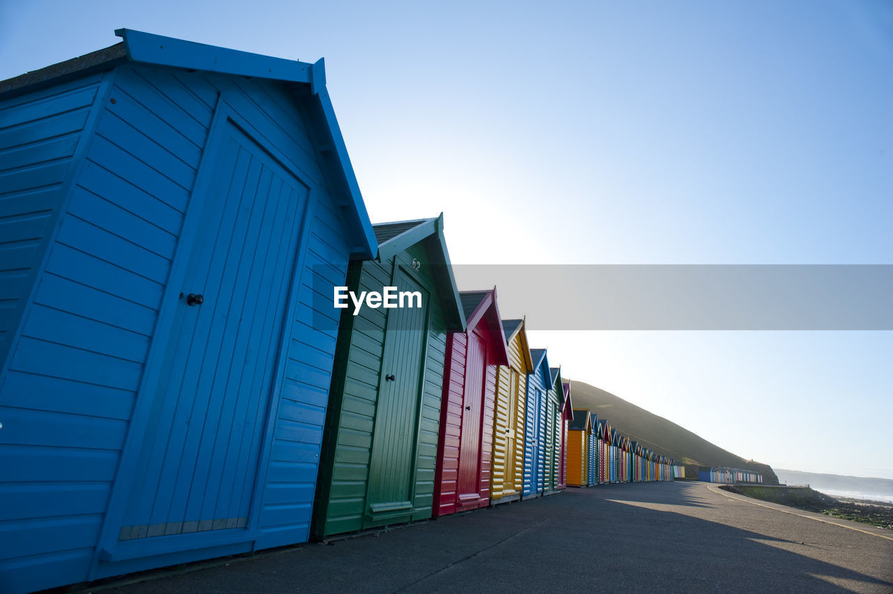 Row Of Colorful Huts At Beach On Sunny Day