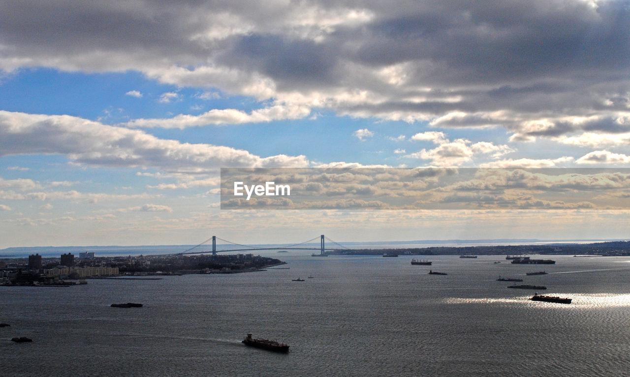 VIEW OF SUSPENSION BRIDGE OVER SEA AGAINST SKY