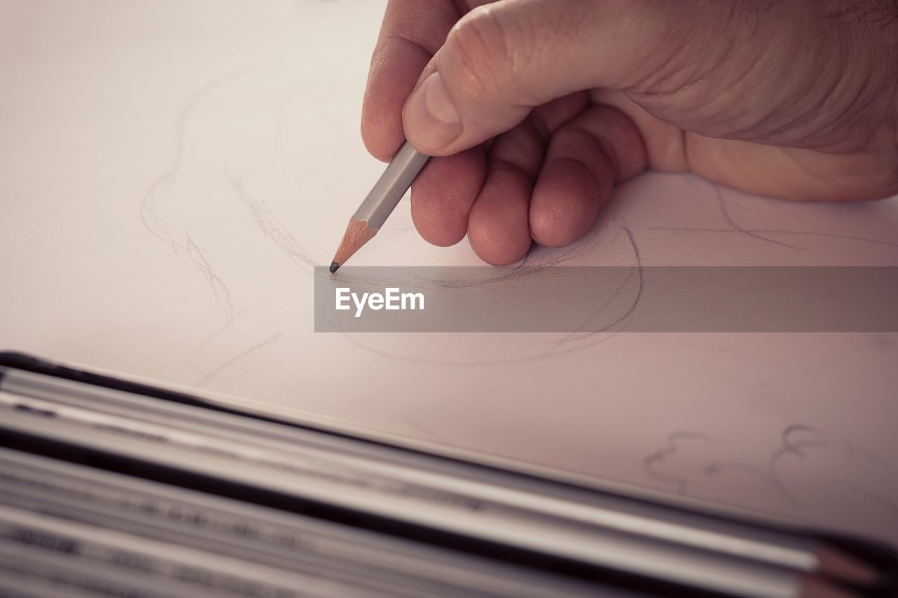 Cropped Hand Of Man Drawing In Paper At Table
