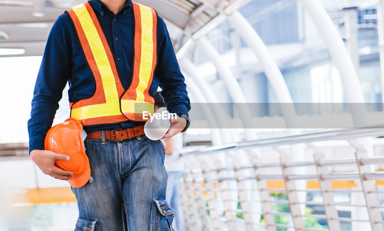 real people, front view, midsection, one person, day, orange color, focus on foreground, casual clothing, men, occupation, working, construction site, standing, holding, architecture, built structure, construction industry, safety, outdoors, jeans
