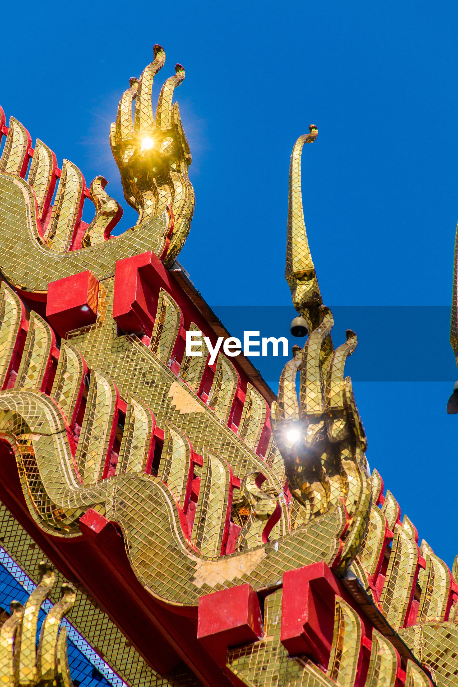 statue, low angle view, sculpture, art and craft, gold colored, no people, blue, outdoors, clear sky, architecture, travel destinations, day, golden color, dragon, gold, building exterior, sky, chinese dragon
