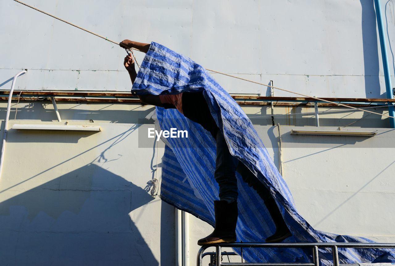 Man Applying Tarpaulin On Rope
