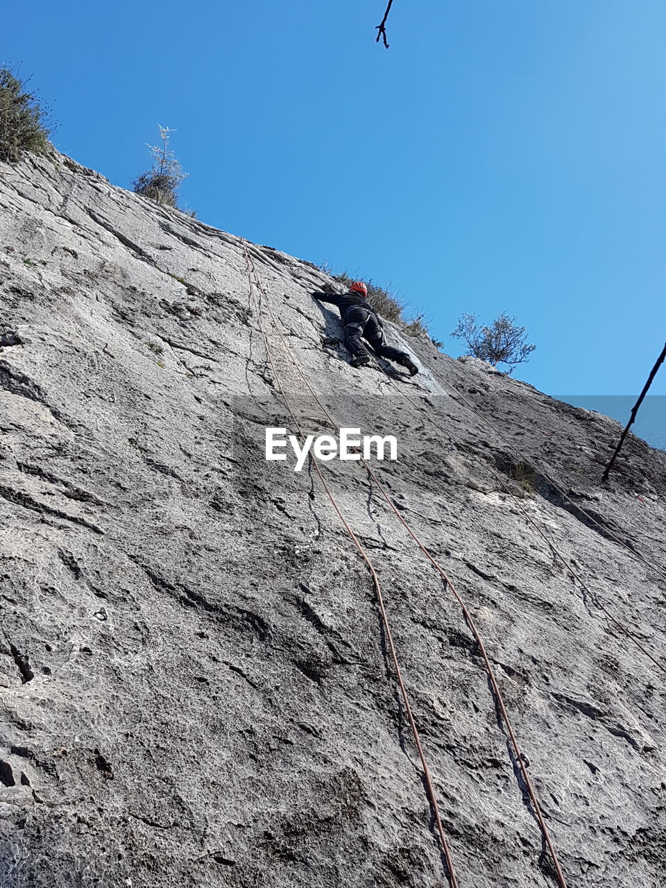 low angle view, rock climbing, climbing, outdoors, day, adventure, clear sky, challenge, mountain, men, real people, one person, rock face, extreme sports, nature, high, people, sky