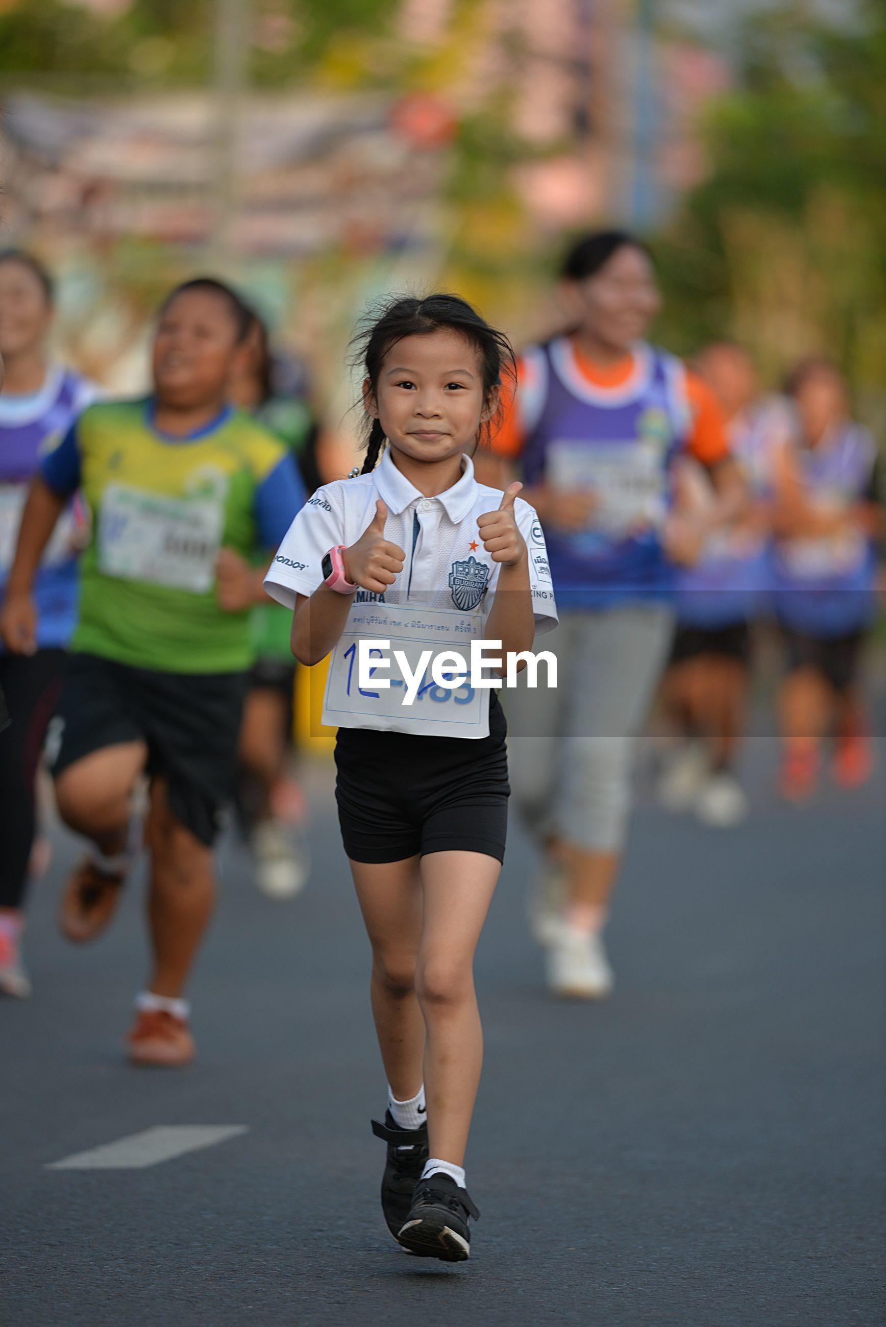 Portrait of girl gesturing while running in marathon