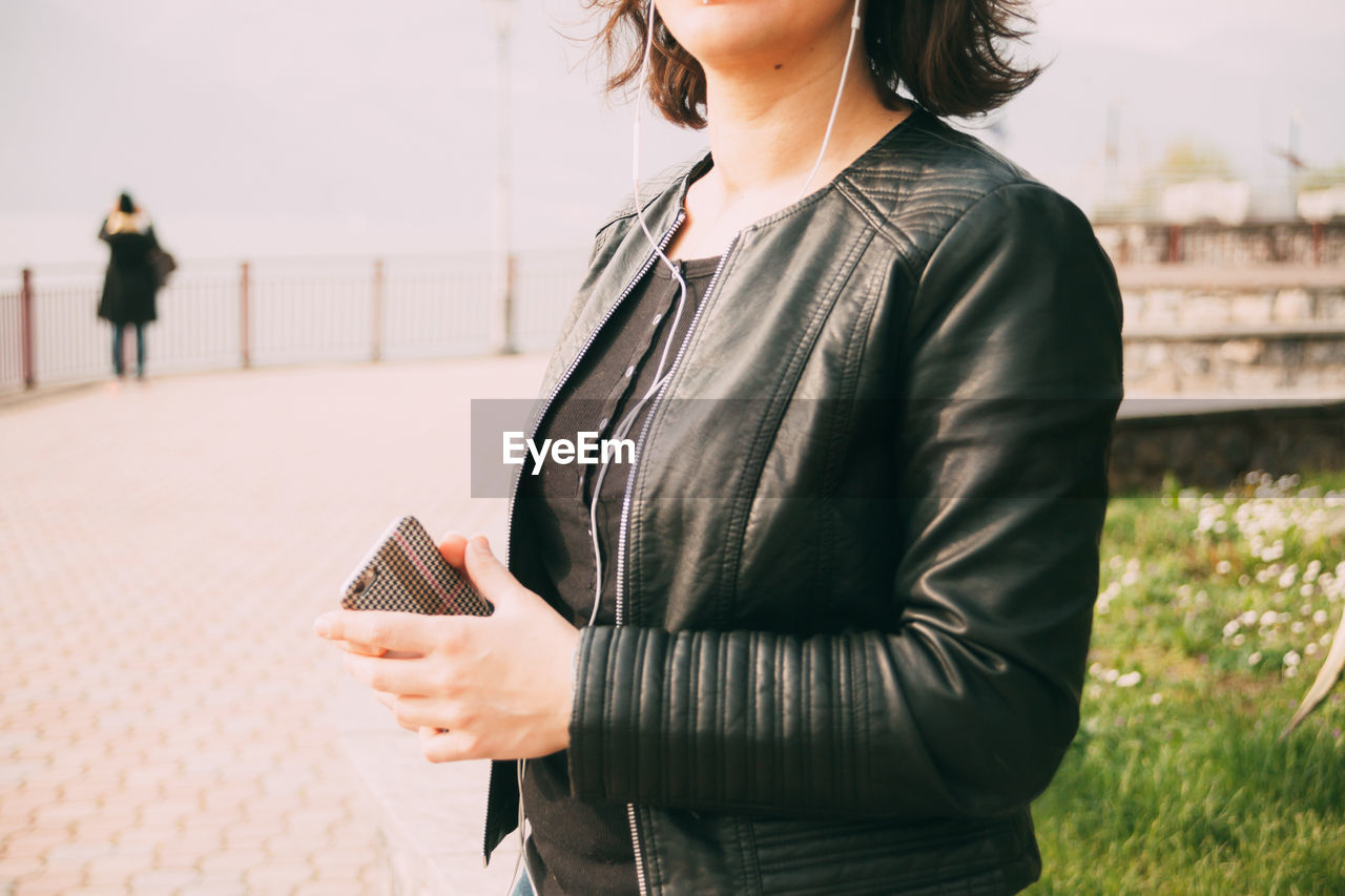 MIDSECTION OF WOMAN HOLDING MOBILE PHONE WHILE STANDING ON SMART