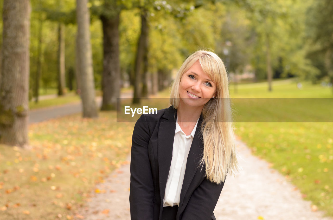 Portrait Of Smiling Beautiful Businesswoman Against Trees At Park