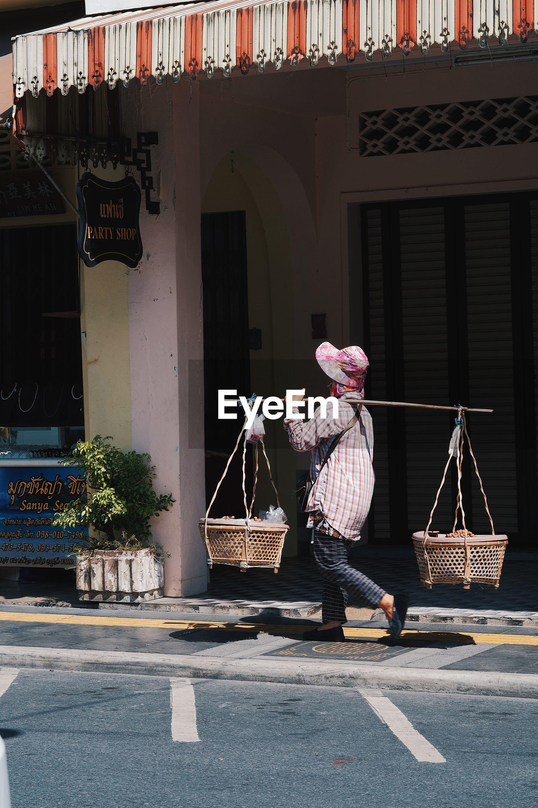 MAN HOLDING BASKET IN STREET