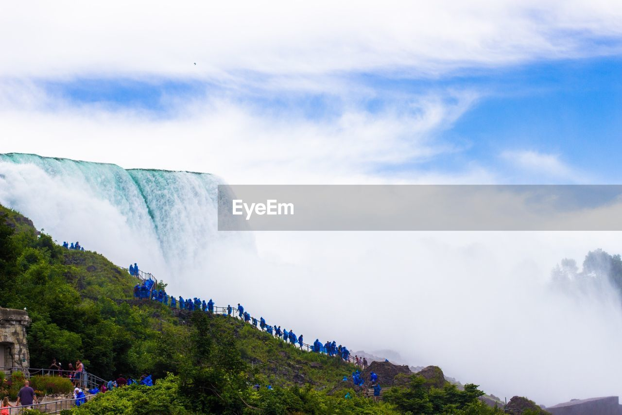 sky, scenics - nature, beauty in nature, mountain, cloud - sky, plant, nature, tree, non-urban scene, day, water, waterfall, tranquil scene, tranquility, travel, outdoors, motion, mountain range, environment, flowing water