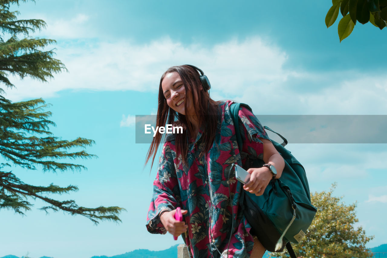 Smiling woman with backpack standing against sky