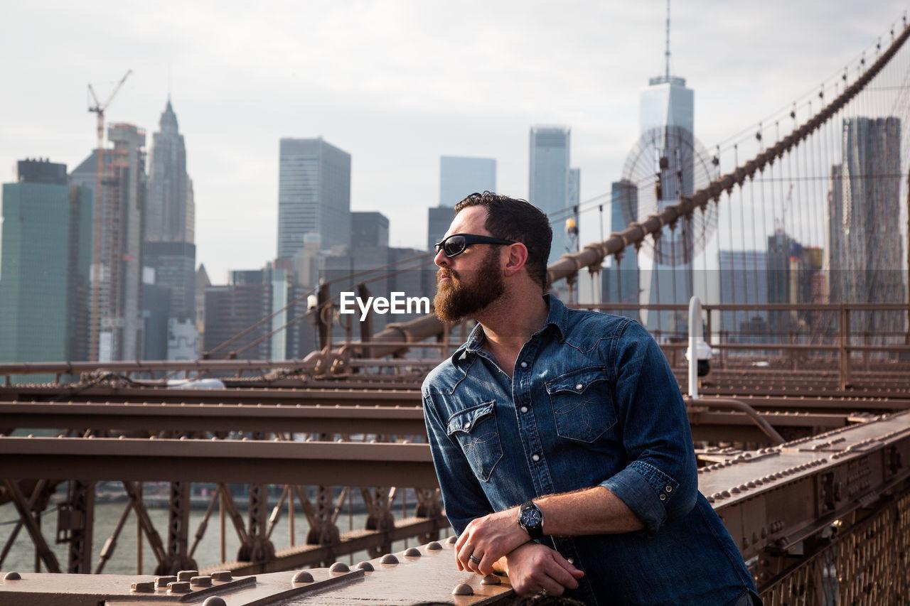 Mature Man Standing On Brooklyn Bridge In City