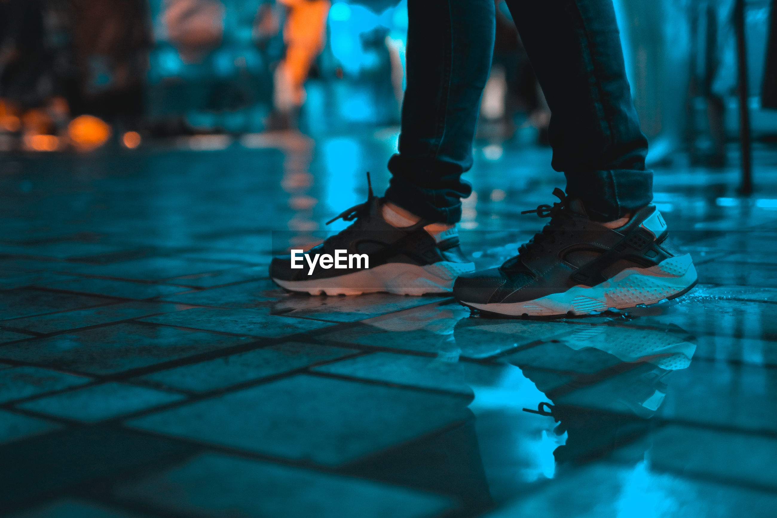 Low section of person standing on wet footpath at night
