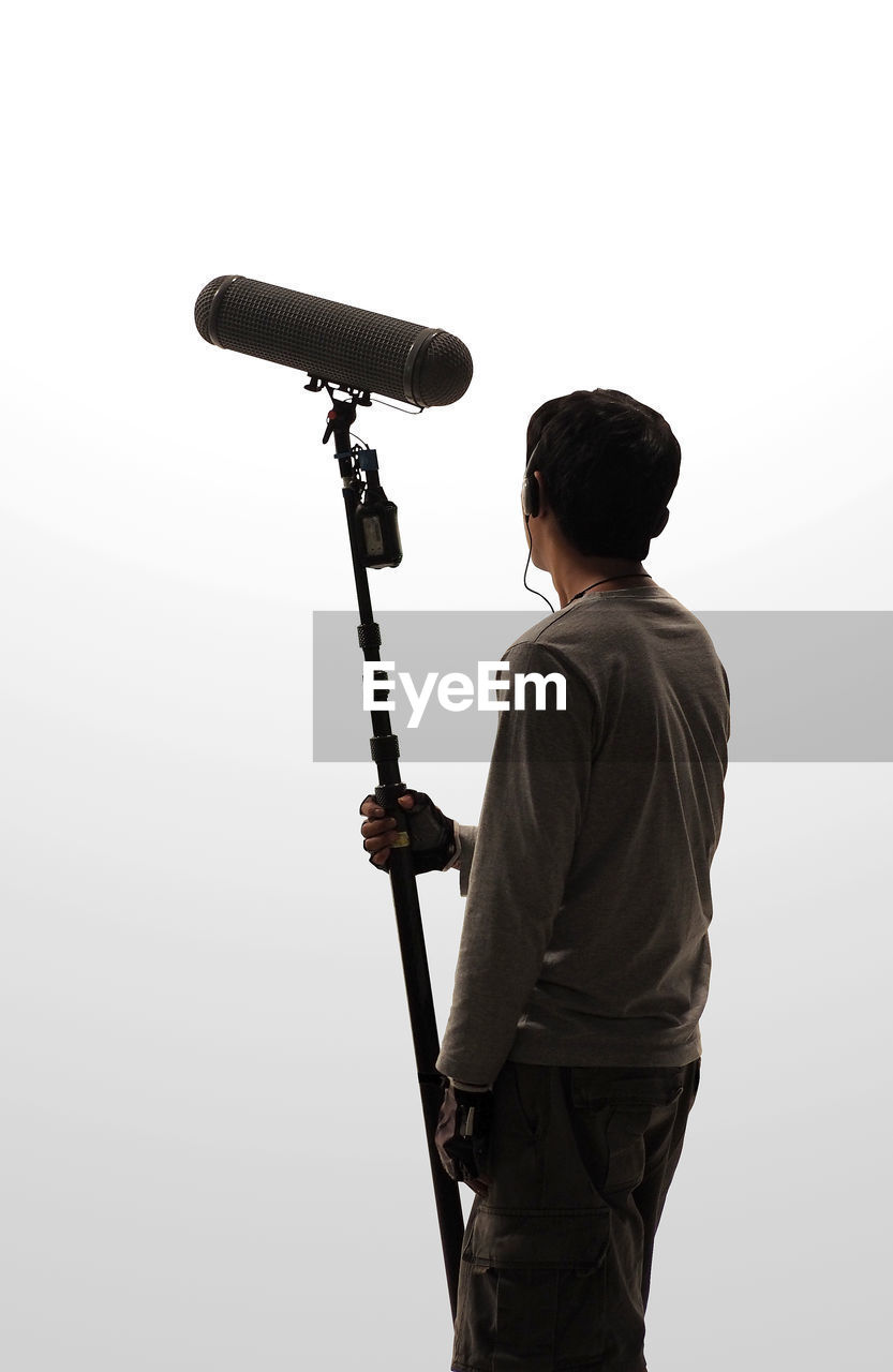 one person, three quarter length, men, real people, lifestyles, holding, rear view, leisure activity, standing, casual clothing, white background, tripod, sky, technology, nature, copy space, photography themes, young men, occupation, photographer