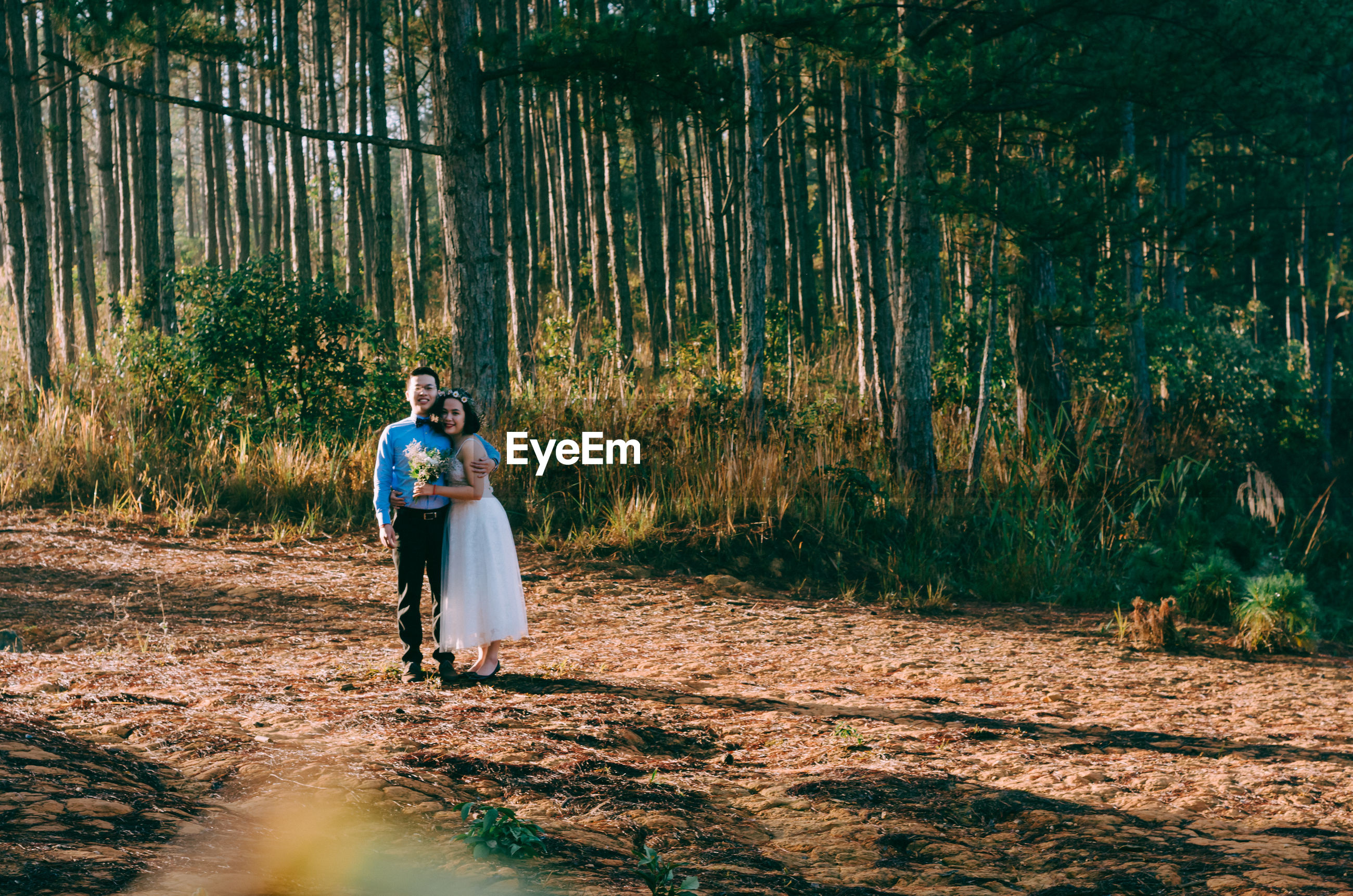 Bride and bridegroom standing in forest