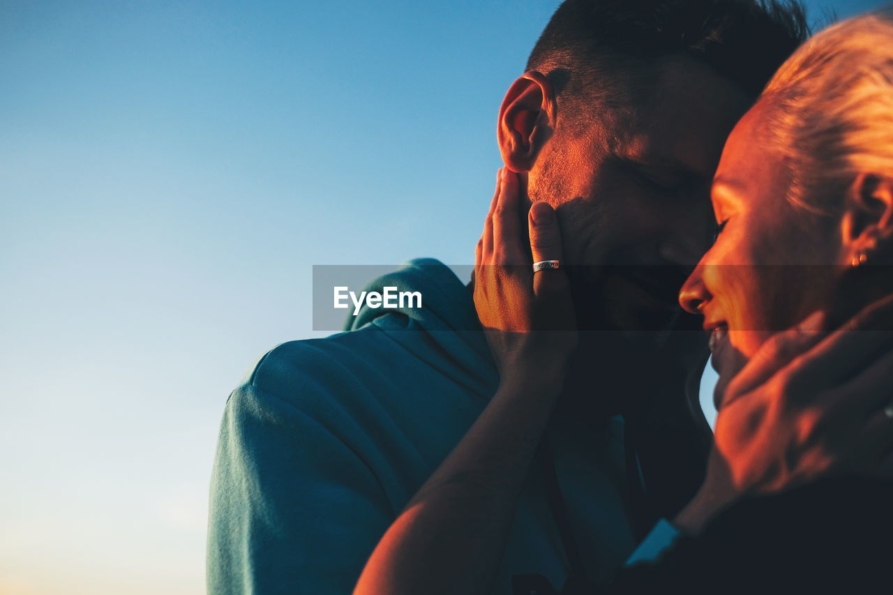 Close-Up Of Couple Embracing Against Blue Sky