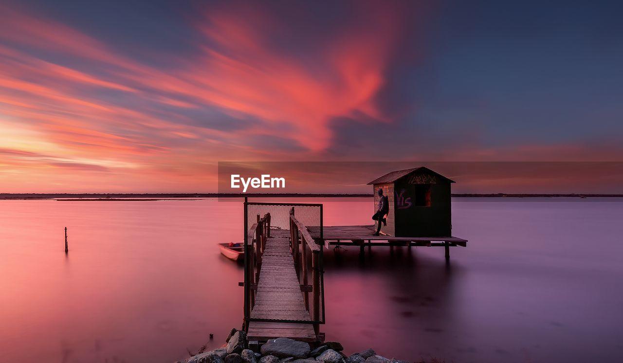 Stilt House In Sea Against Sky During Sunset