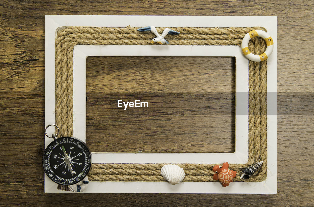 Directly Above Shot Of Frame With Navigational Compass And Shell On Wooden Table