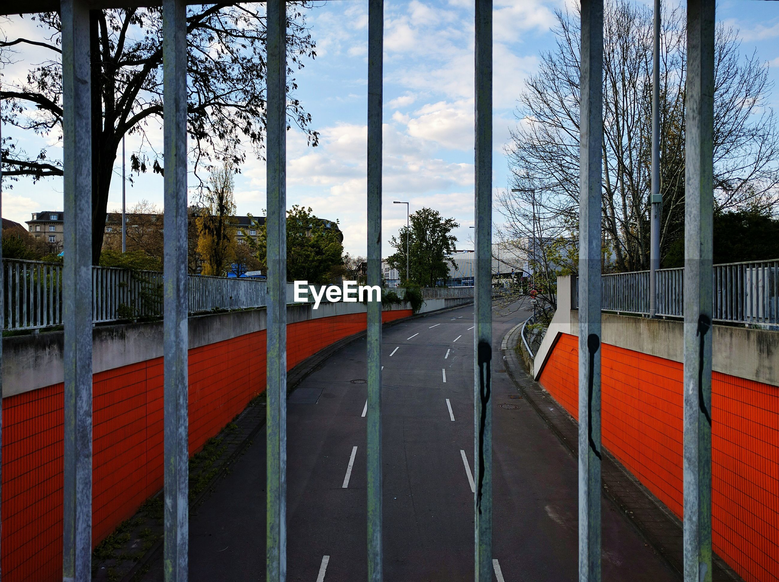 Empty road against sky seen through fence