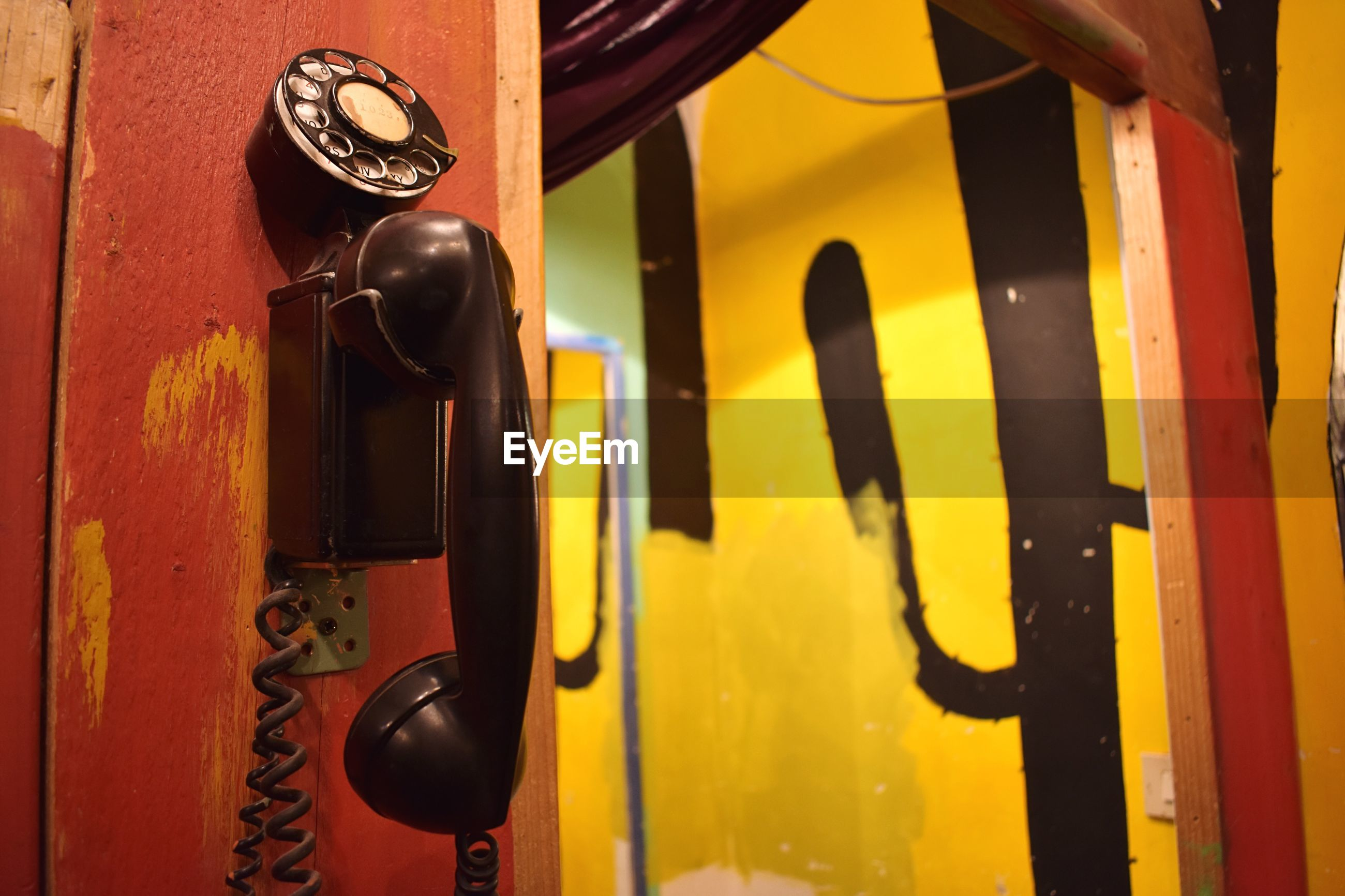 Close-up of rotary phone attached to wall